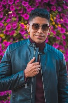 背景にピンクの花を持つ若いラテン系アメリカ人の肖像画。ジーンズ、革のジャケット、茶色の靴