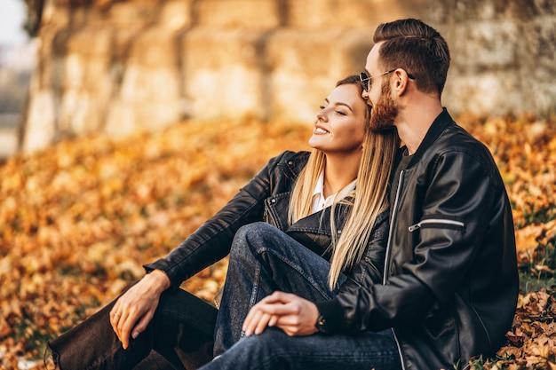 Портрет молодой любящей пары, сидя в осенних листьев и наслаждаясь природой. любовная история