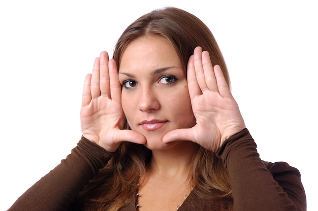Портрет молодой великолепной девушки с естественным макияжем, длинные каштановые волосы, черная футболка, она показывает ладони возле лица