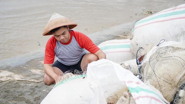 ビーチで漁網を準備している若い男性の漁師の肖像画