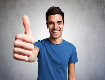 Portrait of a young man giving thumbs up