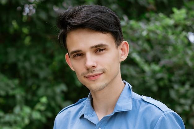 緑の自然な笑顔で青いシャツを着た若い男の肖像画
