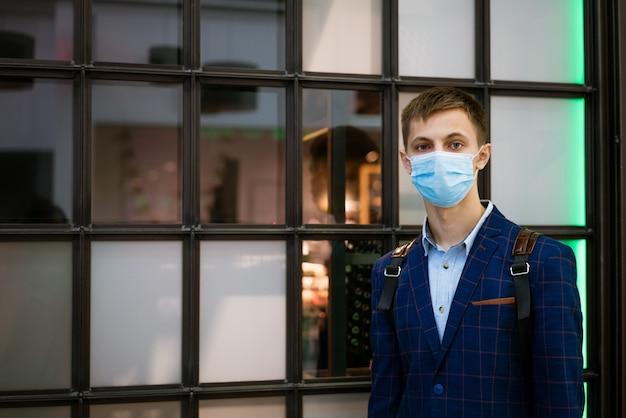 재킷에 젊은 남자와 쇼핑몰에서 의료 마스크의 초상화
