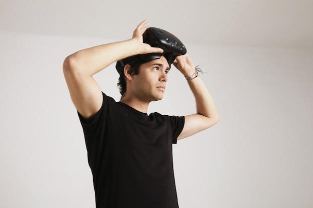 Портрет молодого человека в черной футболке, надевающего гарнитуру vr, изолированную на белом