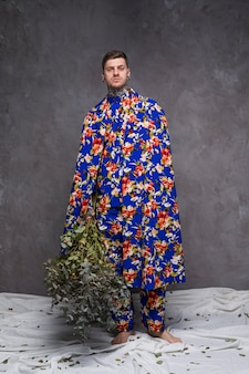 Портрет молодого человека в цветочной одежде, держа веточки зеленого растения, глядя на камеру