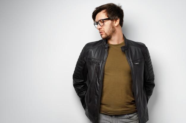 Портрет молодого человека в очках в черной кожаной куртке на сером фоне