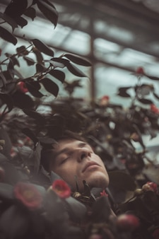 Портрет молодого человека в зеленых листьях. хороший парень стоит у стены зеленых растений. крупный план белого человека в кустах роз.