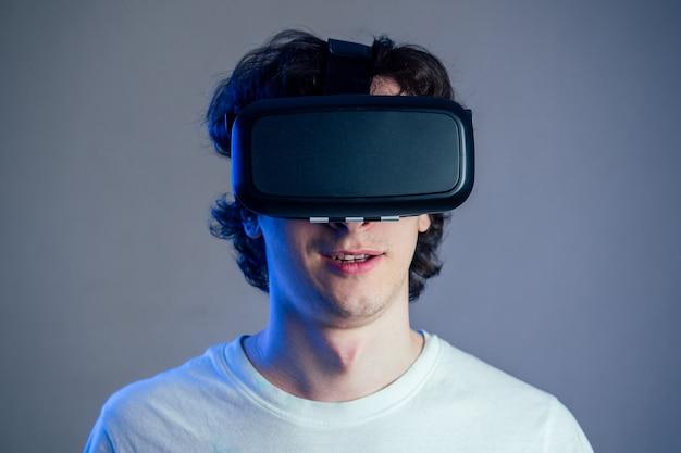 회색 벽 배경에 가상 현실 안경을 쓴 젊은 남자의 초상화. 가상 현실의 가면 속 게임의 개념.
