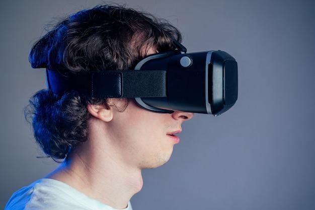 회색 벽 배경에 가상 현실 안경을 쓴 젊은 남자의 초상화. 가상 현실, 게임 및 현대성의 개념