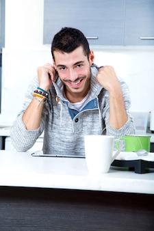タブレットを持って台所で若い男の肖像画。