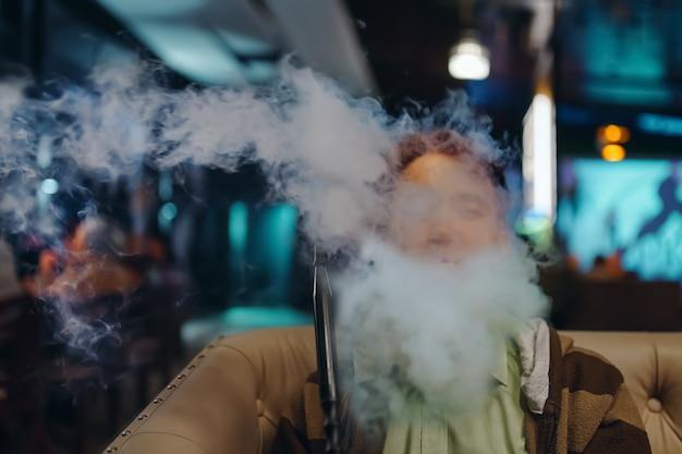煙の中の若い男の肖像画は、レストランで水ギセルの人を喫煙しているシーシャバーでリラックスします...