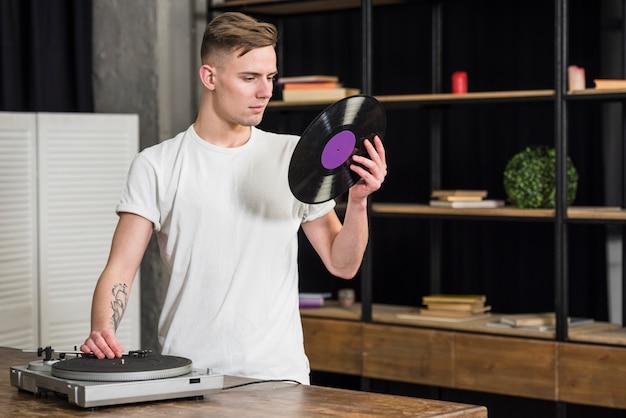 Портрет молодого человека, смотрящего на виниловую пластинку с помощью ретро винилового проигрывателя у себя дома