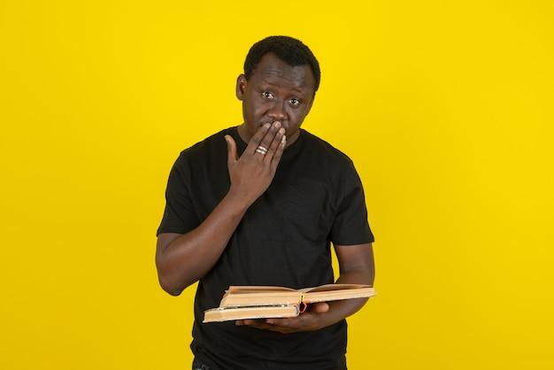 노란 벽에 책을 들고 있는 젊은 남자 모델의 초상화