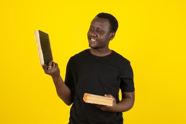 黄色の壁に本を保持している若い男のモデルの肖像画