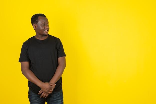 Портрет модели молодого человека, стоящего и смотрящего в сторону против желтой стены