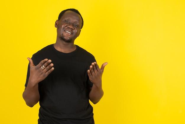 노란색 벽에 서서 카메라를 바라보는 젊은 남자 모델의 초상화