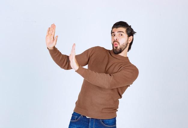 立って架空のオブジェクトを押す若い男のモデルの肖像画。高品質の写真