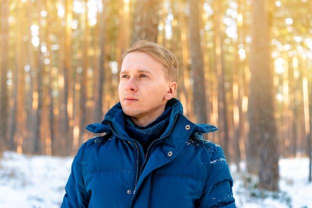 Портрет молодого человека на снежном пейзаже в зимнем сосновом лесу