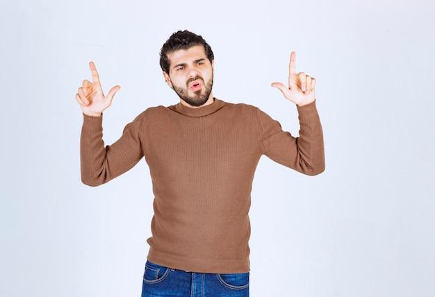 Портрет молодого человека указывая пальцами вверх на космос экземпляра, изолированные на белом фоне. фото высокого качества