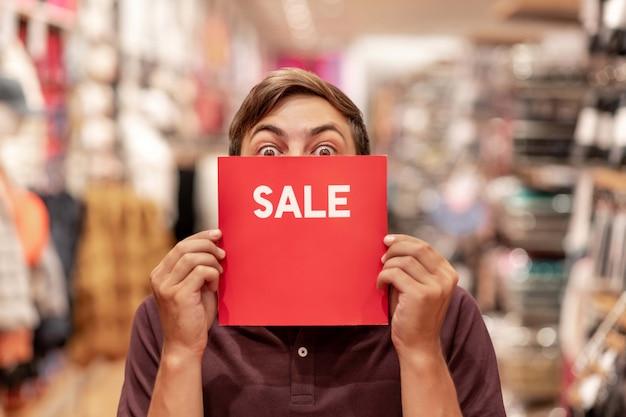 젊은 남자의 초상화 거래 방에 그것으로 그의 얼굴을 덮고 빨간색 판매 기호로 포즈. 판매. 할인. 미친 할인. 기쁨의 감정.