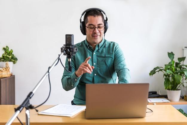 Портрет молодого человека, ведущего подкаст в прямом эфире из своего дома, и он сидит за столом с ноутбуком