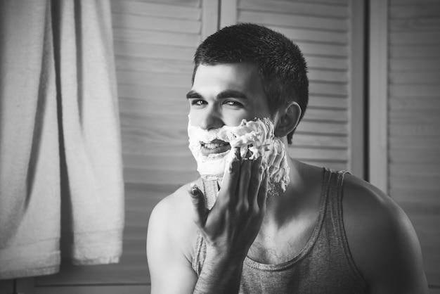 아침 위생 동안 화장실에서 그의 얼굴을 면도하는 젊은 남자의 초상화