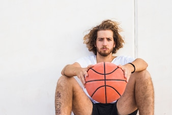 Portrait of a young man sitting with basketball