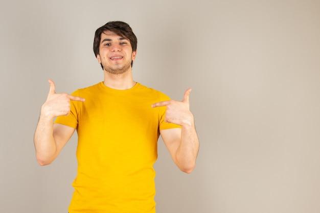 立って灰色に対して自分自身を指している若い男の肖像画。