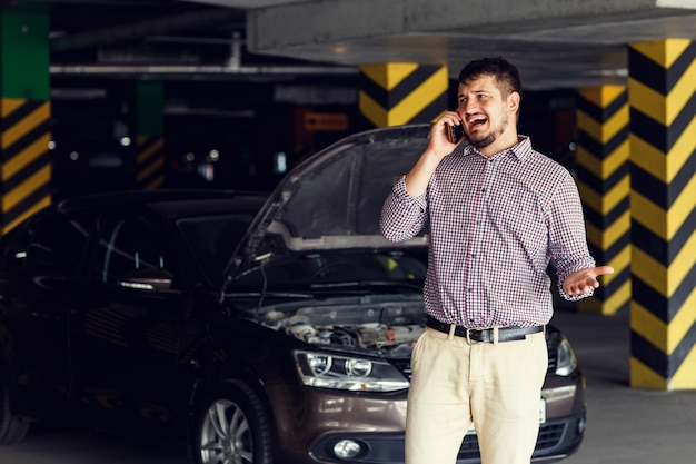 壊れた車の前に立って携帯電話で話している若い男の肖像画は助けを求めています