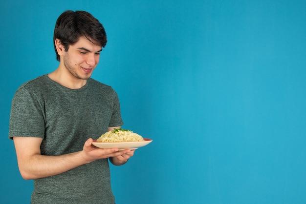 Портрет молодого человека, стоящего с тарелкой вкусной лапши.