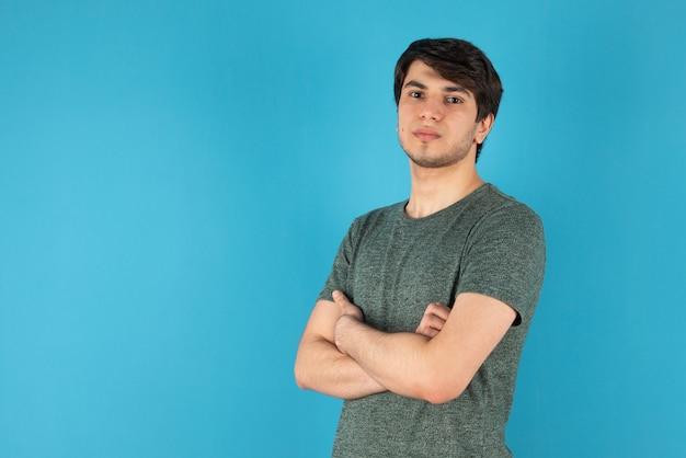 Портрет молодого человека, стоящего со скрещенными руками на синем фоне.