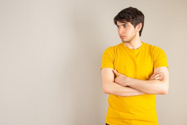 Портрет молодого человека, стоящего со скрещенными руками на сером фоне.