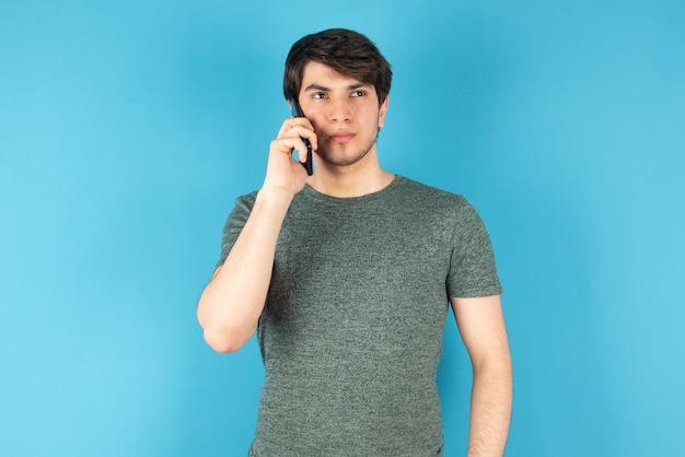 Портрет молодого человека разговаривает по мобильному телефону против синего цвета.