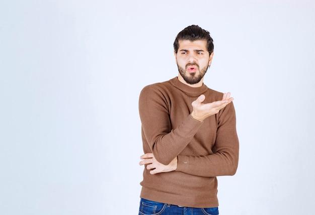 考えて白い壁に立っている若い男の肖像画。