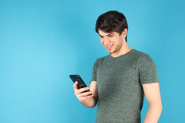 青に対して携帯電話を使用して若い男の肖像画。