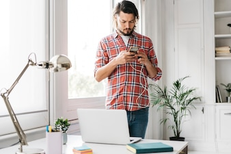 Portrait of a young man using mobile phone standing near the desk with laptop