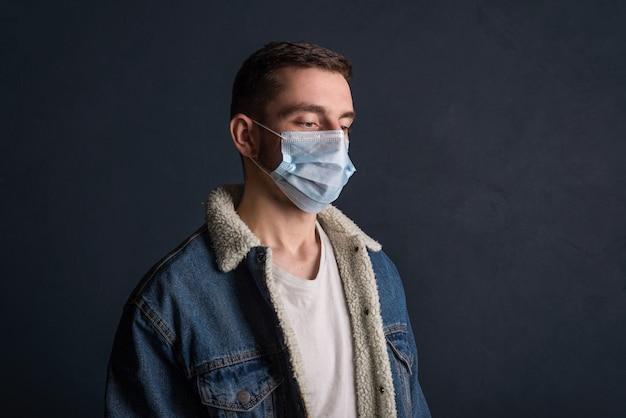 暗い灰色の表面に医療マスクを身に着けている若い男の肖像画