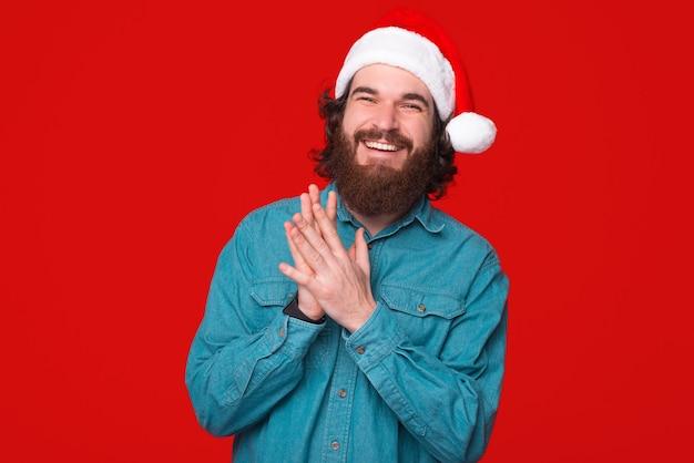 크리스마스 모자를 쓰고 젊은 남자의 초상화는 카메라에 웃 고있다.