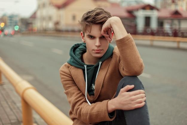 거리에 까마귀와 트렌디 한 코트에 머리를 가진 젊은 남자의 초상화