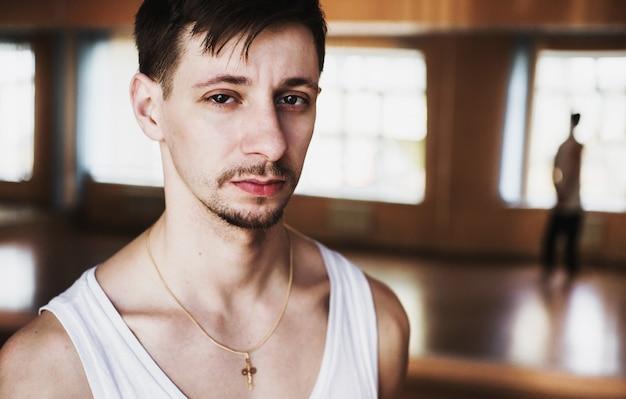 トレーニングルームで白いtシャツを着た口ひげとあごひげを持つ若い男の肖像画。