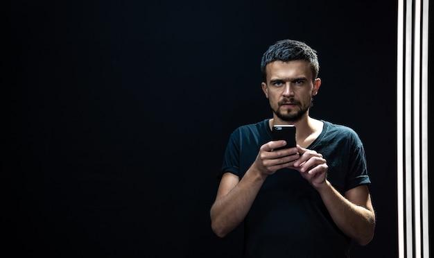 어둠 속에서 그의 손에 전화를 가진 젊은 남자의 초상화.