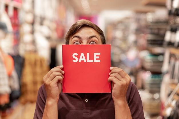 赤い販売サインと若い男の肖像画