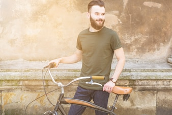 Portrait of a young man with bicycle looking away