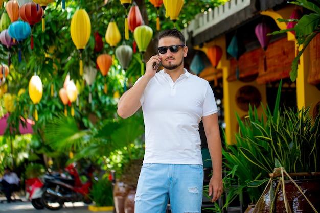 Портрет молодого человека в очках, прогулки на свежем воздухе с мобильным телефоном. мужчина с телефоном. счастливый человек разговаривает по телефону.
