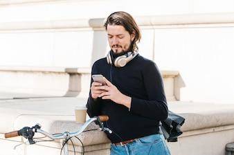 Портрет молодого человека с наушниками на шее с помощью мобильного телефона на открытом воздухе