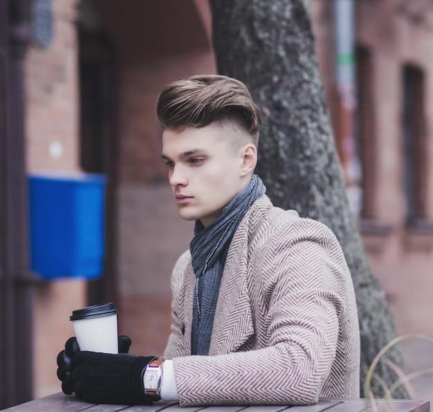 Портрет молодого менеджера в деловом стиле в городе с кофе
