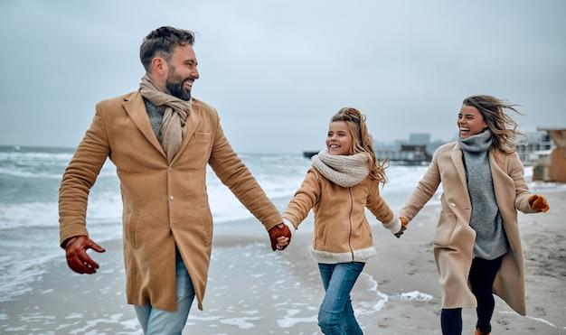 冬に暖かい服とスカーフを身に着けて冬にビーチで楽しんでいる若い夫婦とそのかわいい娘の肖像画。