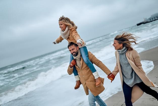 冬のビーチで楽しんでいる若い夫婦とそのかわいい娘の肖像画。
