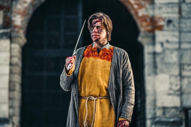 彼の肩に剣と顔の傷を持つ鎧の若い中世の戦士の肖像画。城の近くの戦いの過程で