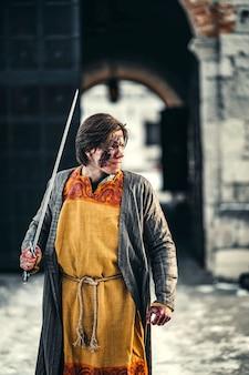 彼の肩に剣と顔に傷を持つ鎧を着た若い中世の戦士の肖像画。戦いの最中、城の近く